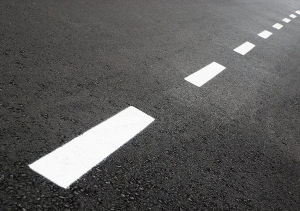 White divider lines on black pavement show the road from happiness to well being
