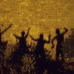 Shadows of ancient tribal dancers illuminate a blazing yellow wall