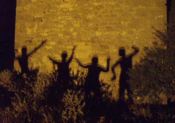 Shadows of ancient tribal dancers illuminate a blazing yellow wall