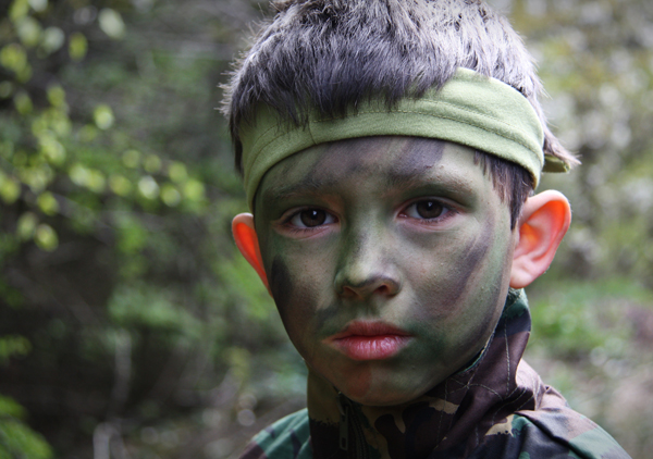 A young man in military face paint portrays a violent culture