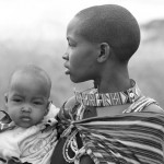 Tribal mother in traditional robe swaddles her baby