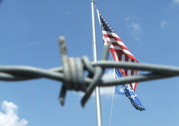 The U.S. Flag waves behind a barb wire fence