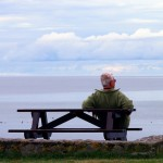 An older man sits on a bench staring at the sea in contemplation